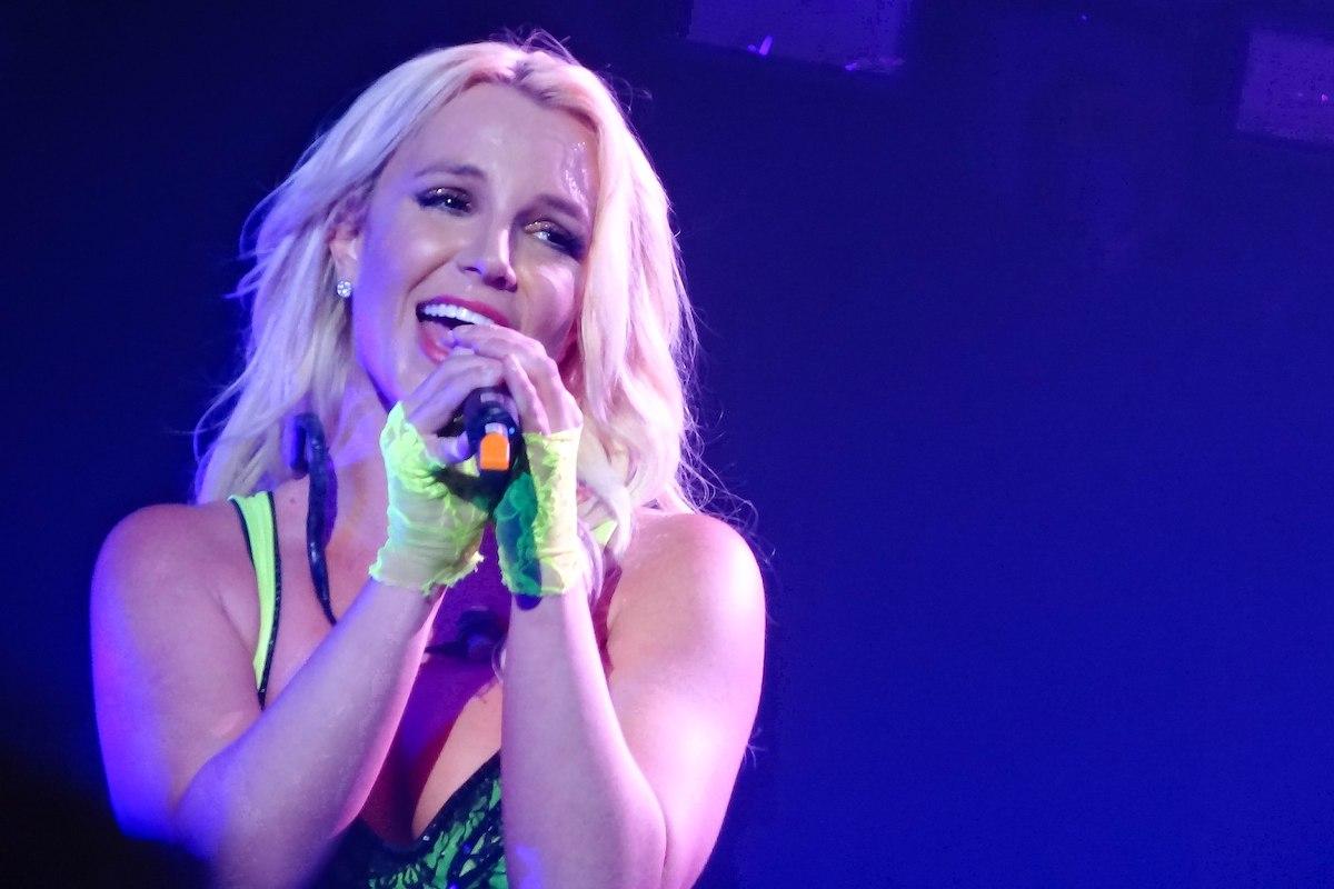 Britney Spears singing in a spotlight.