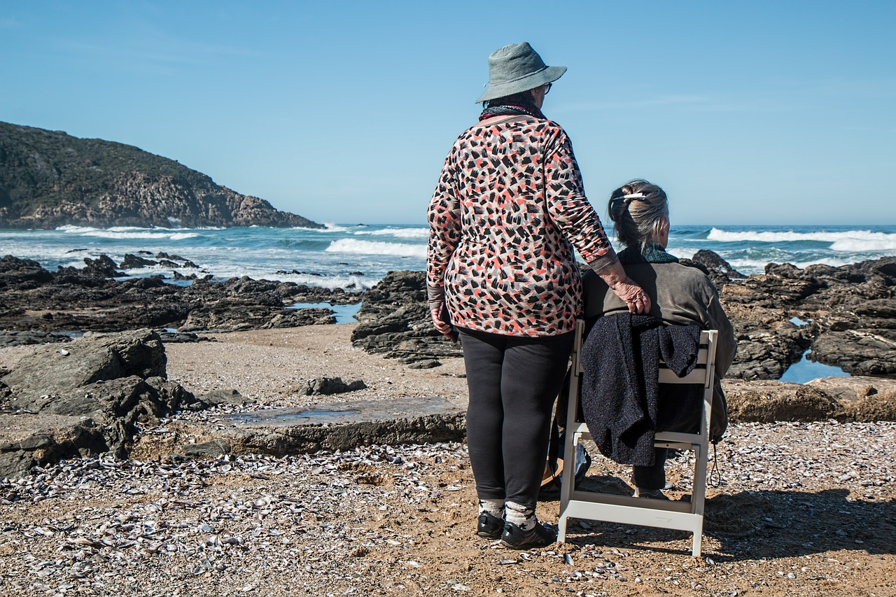 Two elderly women at the coast together watching the waves
