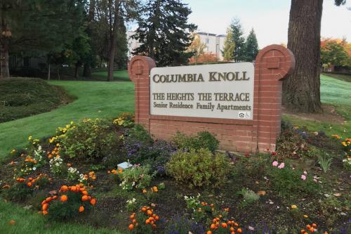 A sign in a bed of flowers reads The Heights at Columbia Knoll, with a building in the background on well kept landscape.