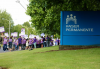 A large group of people wearing purple shirts and holding labor union signs stand in front of Kaiser building.